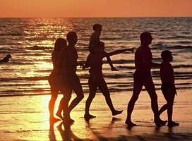 Group of friends walking on beach at sunset