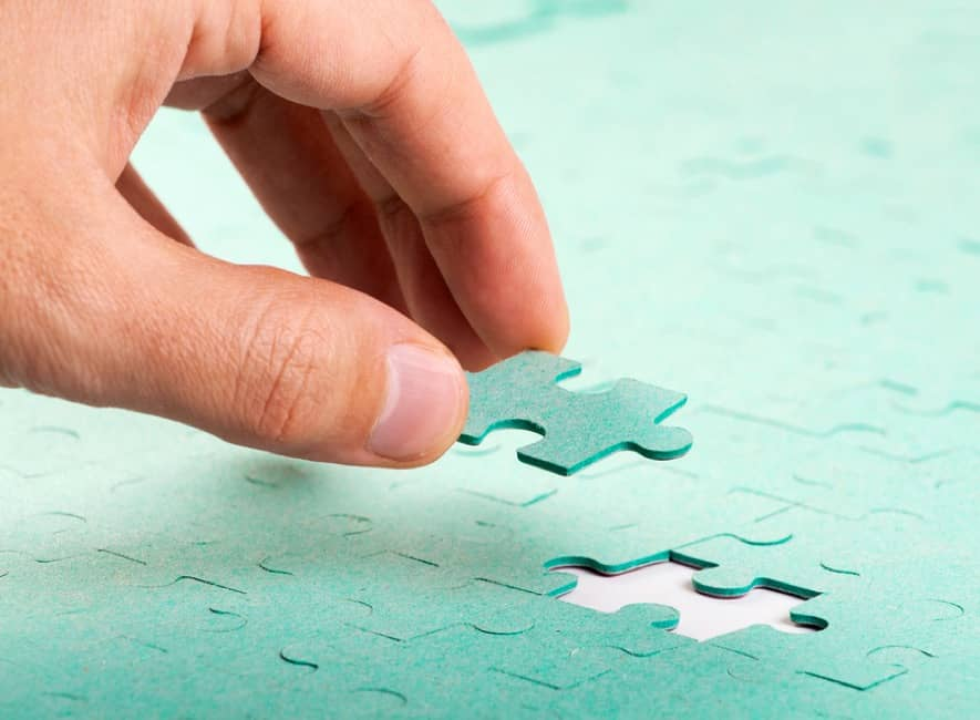 Human hand placing last piece of a jigsaw puzzle