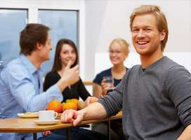 Four seated business people discuss ideas