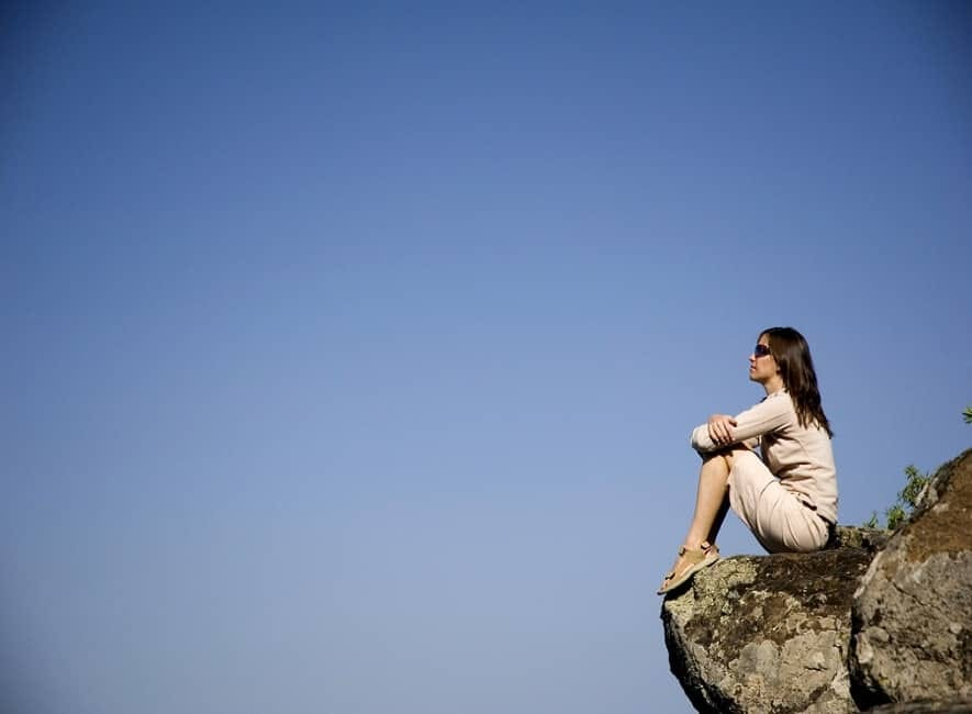 Photo of woman sitting on cliff looking our over blue sky
