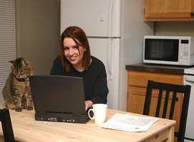 Female business owner with laptop and pet cat