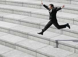 Happy man jumping down wide steps