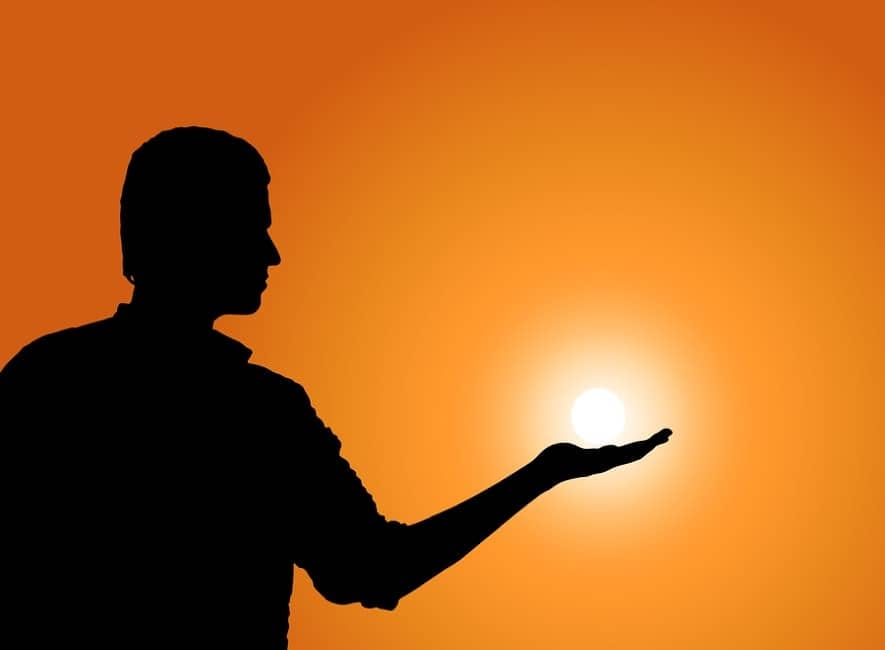 Sunset silhouette trick picture of man holding sun