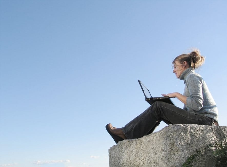 Girl sitting on boulder with laptop computer, blue sky