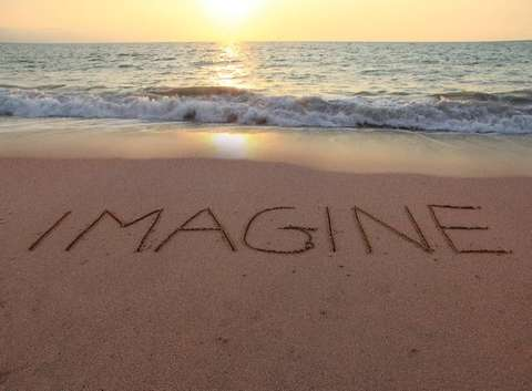 Photo of beautiful sandy seashore with the word Imagine written in the sand