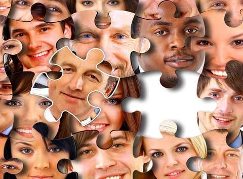 Jigsaw puzzle pieces with each piece showing a person's face