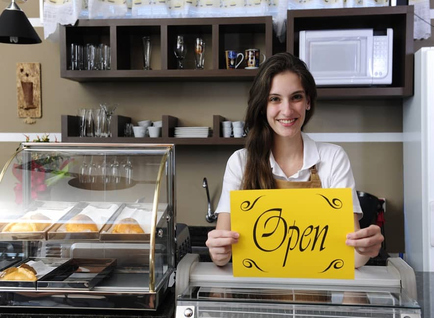 Smiling female business owner with Open sign