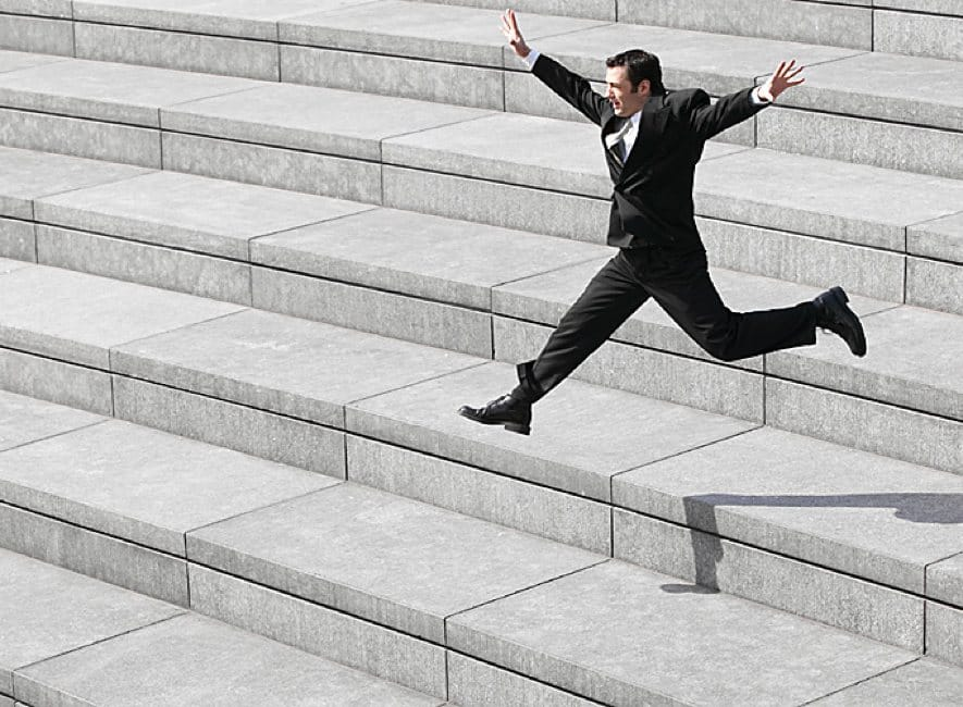 Happy man leaping down public building stone steps