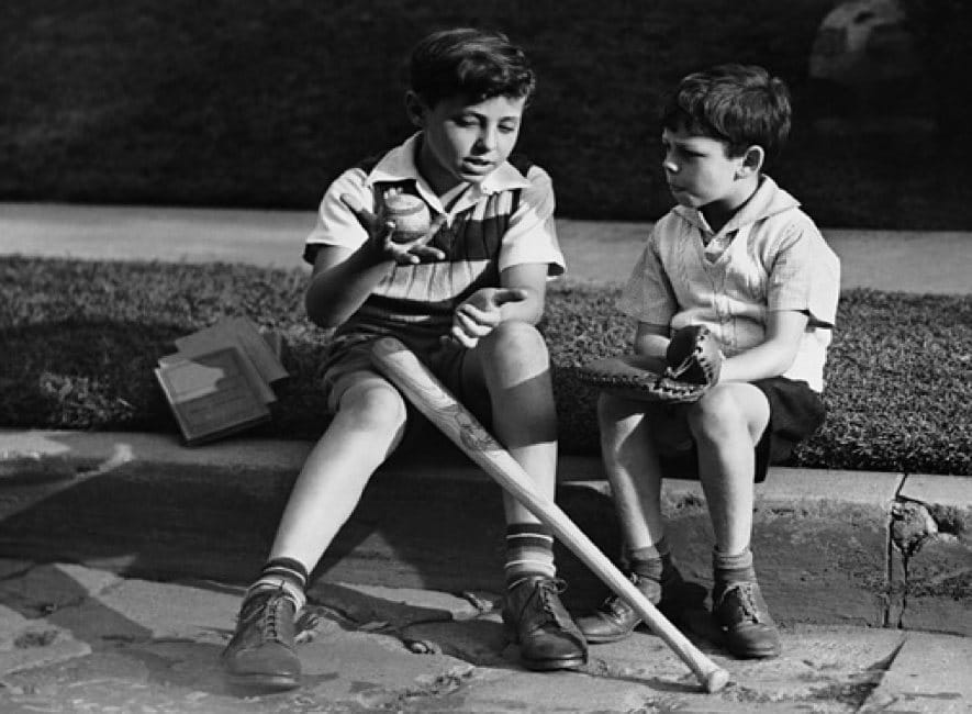 Two boys talking sitting on sidewalk with baseball and bat