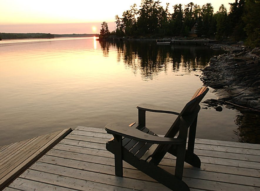Single deck-chair looking over calm sunset lake view