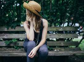 Young woman sitting on park bench deep in thought