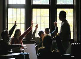 Teacher and class of students with hands up to answer