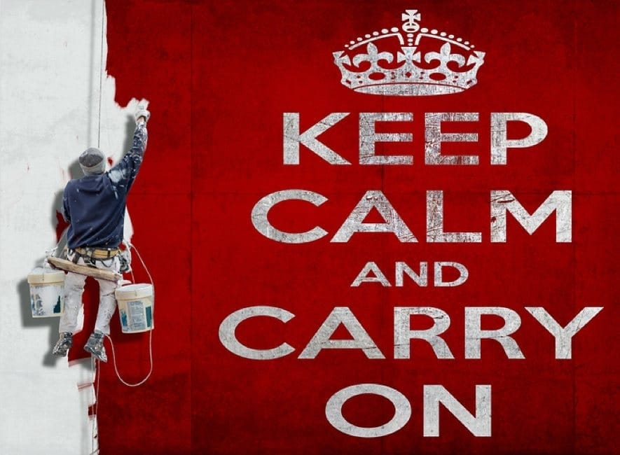 Man painting large wall sign keep calm and carry on