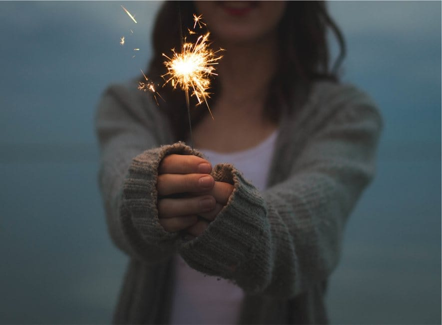 Young woman holding up a lit firework sparkler
