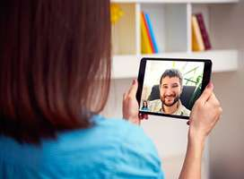 Woman talking with man using tablet device video chat