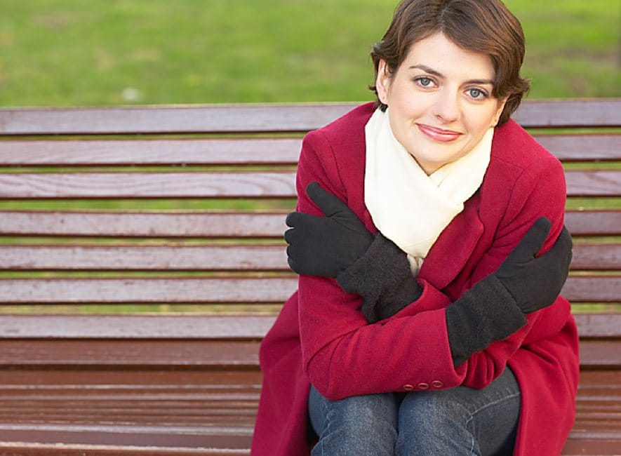 Thoughtful smiling woman sitting on part bench