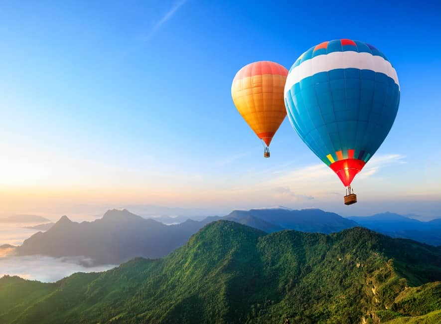 Two hot air ballons flying over idyllic landscape