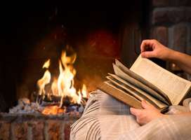 Person sat next to a nice open fire reading a book