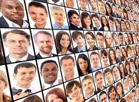 A large TV screen of many business people headshots