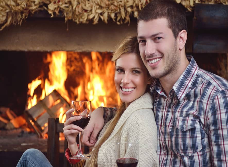 Couple enjoying glass of wine in front of open fireplace